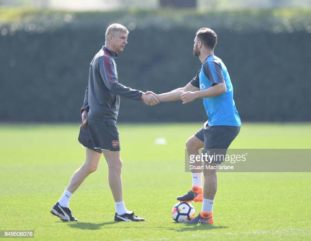 Arsenal manager Arsene Wenger shakes hands with Shkodran Mustafi before a training session at London Colney on April 21 2018 in St Albans England