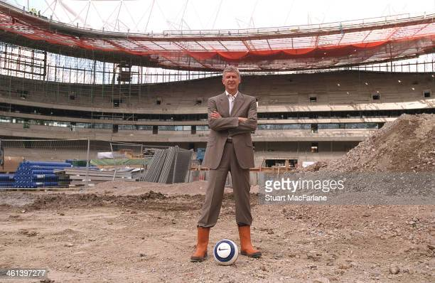 Arsenal manager Arsene Wenger stands on the centre spot of Emirates stadium during construction on August 15 2005 in London England