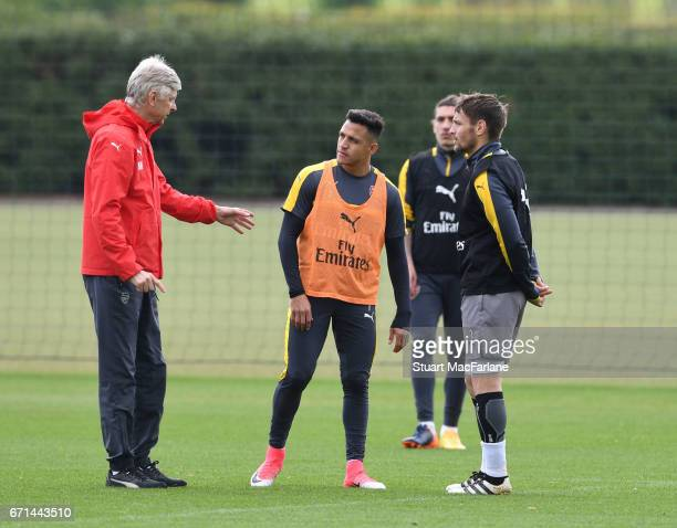Arsenal manager Arsene Wenger talks to Alexis Sanchez and Mathieu Debuchy during a training session at London Colney on April 22 2017 in St Albans...