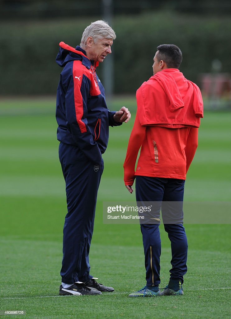 Arsenal manager Arsene Wenger talks to Alexis Sanchez before a training session at London Colney on October 23, 2015 in St Albans, England.