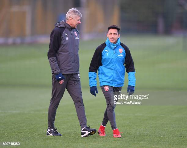 Arsenal manager Arsene Wenger talks to Alexis Sanchez before a training session at London Colney on December 30 2017 in St Albans England