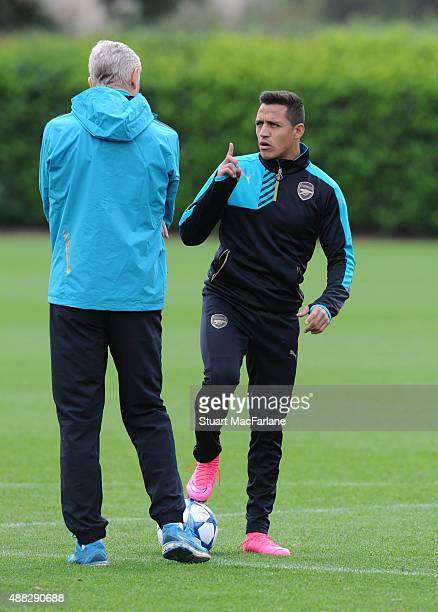Arsenal manager Arsene Wenger talks to Alexis Sanchez during a training session at London Colney on September 15, 2015 in St Albans, England.