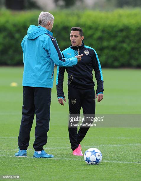 Arsenal manager Arsene Wenger talks to Alexis Sanchez during a training session at London Colney on September 15 2015 in St Albans England
