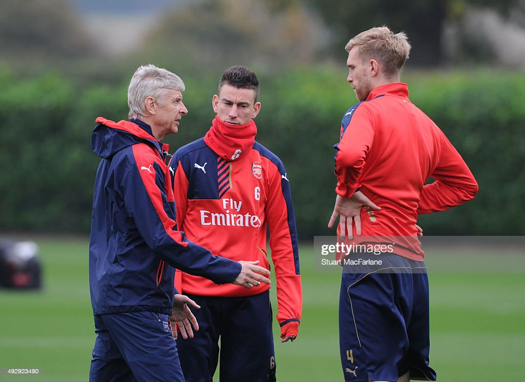 Arsenal manager Arsene Wenger talks to (2ndR) Laurent Koscielny and (R) Per Mertesacker during a training session at London Colney on October 16, 2015 in St Albans, England.