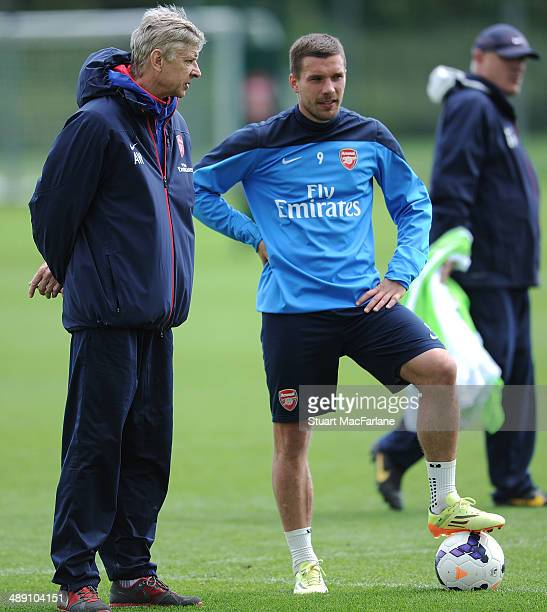 Arsenal manager Arsene Wenger talks to Lukas Podolski during a training session at London Colney on May 10, 2014 in St Albans, England.