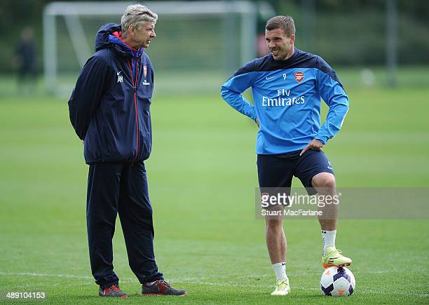 Arsenal manager Arsene Wenger talks to Lukas Podolski during a training session at London Colney on May 10 2014 in St Albans England