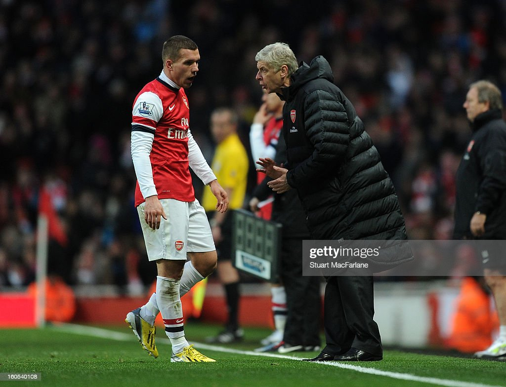 Arsenal manager Arsene Wenger talks to Lukas Podolski during the Barclays Premier League match between Arsenal and Stoke City at Emirates Stadium on February 02, 2013 in London, England.