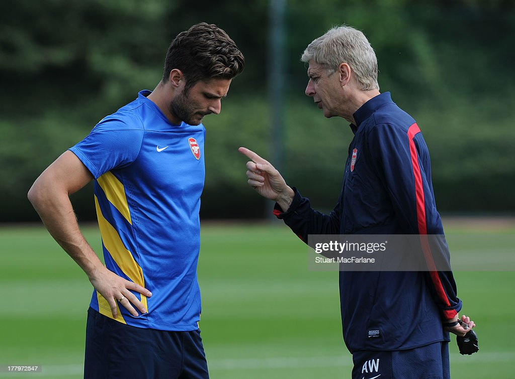 Arsenal manager Arsene Wenger talks to Olivier Giroud before a training session ahead of their UEFA Champions League Play Off second leg match against Fenerbache at London Colney on August 26, 2013 in St Albans, England.