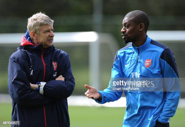 Arsenal manager Arsene Wenger talks with Abou Diaby during a training session at London Colney on April 27 2014 in St Albans England