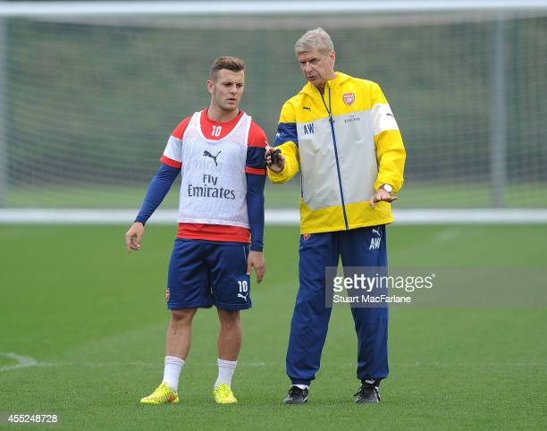 Arsenal manager Arsene Wenger talks with Jack Wilshere during a training session at London Colney on September 11, 2014 in St Albans, England.