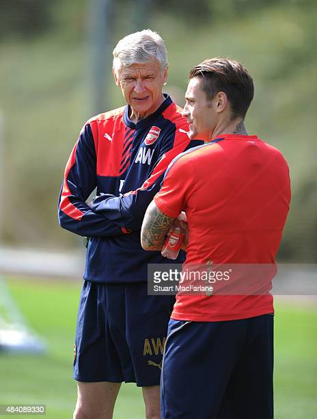 Arsenal manager Arsene Wenger with defender Mathieu Debuchy during a training session at London Colney on August 15 2015 in St Albans England