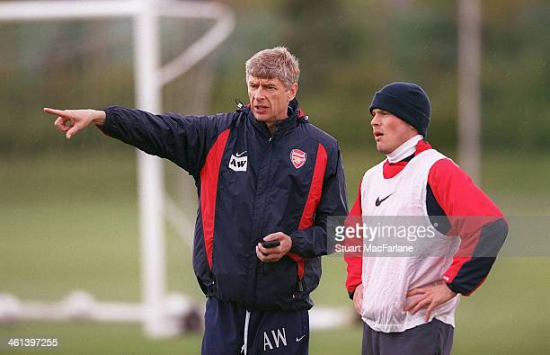 Arsenal manager Arsene Wenger with Freddie Ljungberg during a training session at London Colney on April 15 2003 in St Albans England