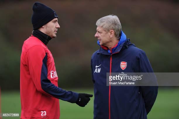Arsenal manager Arsene Wenger with Nicklas Bendtner during a training session at London Colney on November 29 2013 in St Albans England