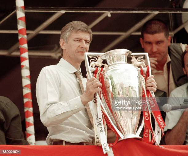 Arsenal manager Arsene Wenger with the League trophy while on the bus parade after doing the League and Cup double on May 17, 1998 in London, England.