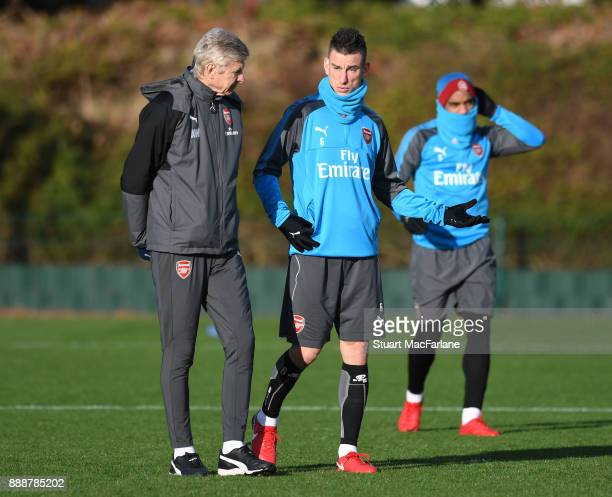 Arsenal manager Arsenen Wenger talks to Laurent Koscielny before a training session at London Colney on December 9 2017 in St Albans England