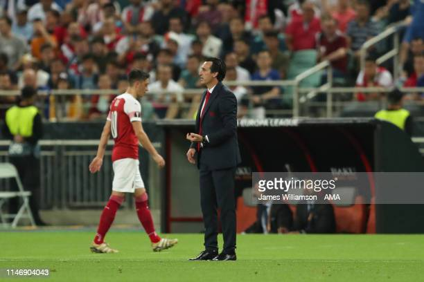 Arsenal manager \ Head coach Unai Emery looks on as the subsituted Mesut Ozil of Arsenal walks by during the UEFA Europa League Final between Chelsea...