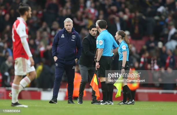 Arsenal manager Mikel Arteta shakes hands with the officials at the end of the game as West Ham United manager David Moyes looks on during the...