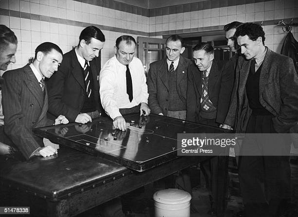 Arsenal manager Tom Whittaker demonstrating a plan on the tactics table during a meeting with the team in the dressing room at Highbury Stadium North...