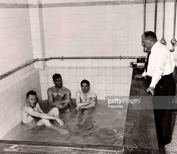Arsenal manager Tom Whittaker talks to left to right Jimmy Logie Alf Fields and Alex Forbes in the bath after a match at Highbury in London circa...