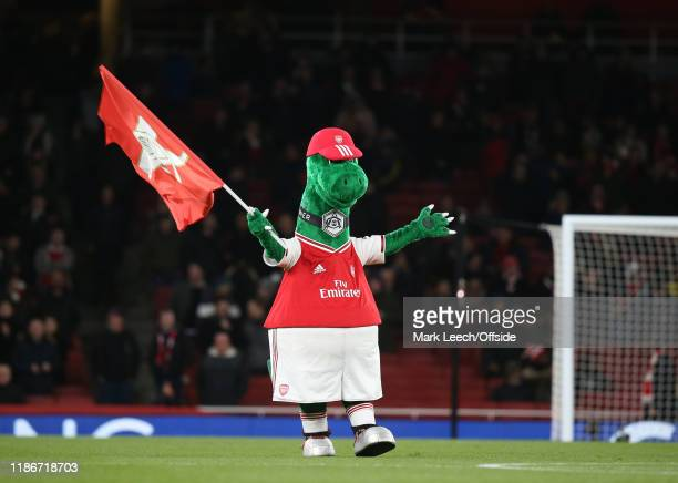 Arsenal mascot Gunnersaurus waves a flag before the Premier League match between Arsenal FC and Brighton Hove Albion at Emirates Stadium on December...