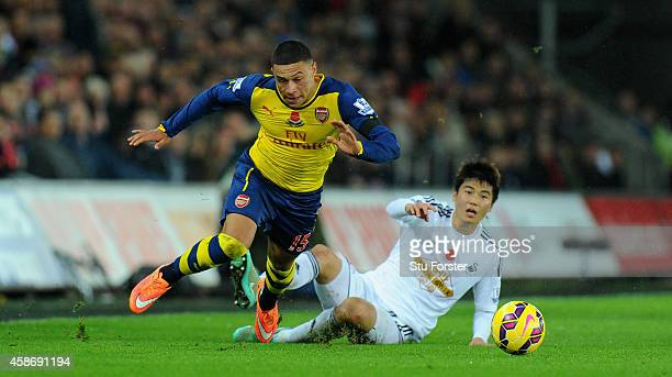 Arsenal player Alex OxladeChamberlin is fouled by Ki SungYueng during the Barclays Premier League match between Swansea City and Arsenal at Liberty...