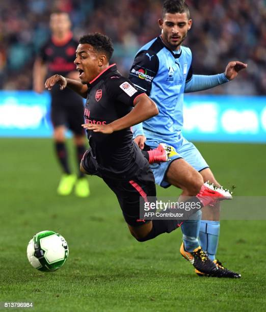 Arsenal player Donyell Malen battles for the ball with Sydney FC player Nicola Kuleski in their football friendly played in Sydney on July 13 2017 /...