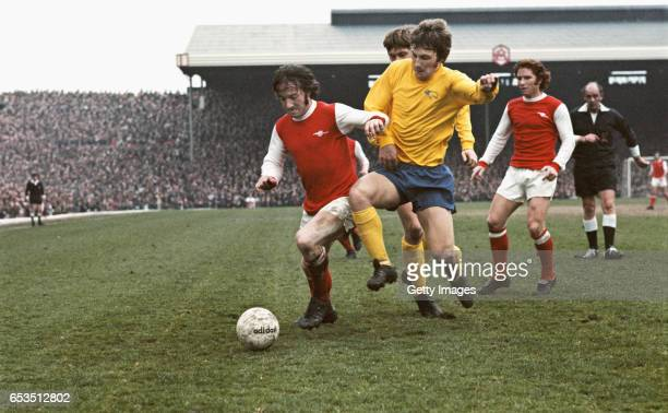 Arsenal player George Armstrong holds off the challenge of Derby defender Colin Todd as Alan Ball looks on during a First Divsion match between...