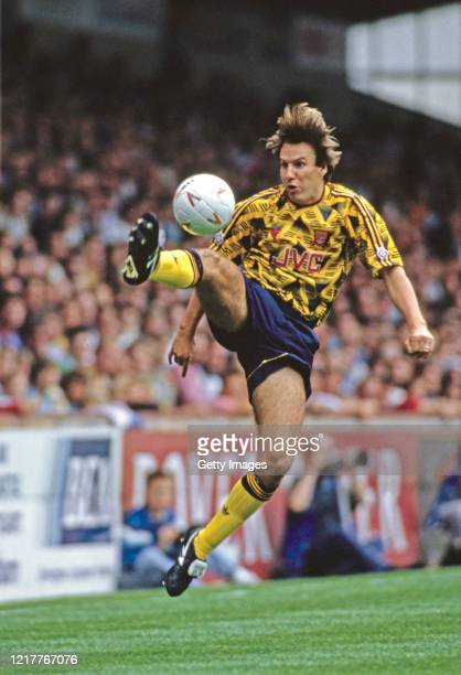 Arsenal player Paul Merson controls the ball in mid-air wearing the yellow and blue JVC away kit during a match circa 1992 in England, United Kingdom.