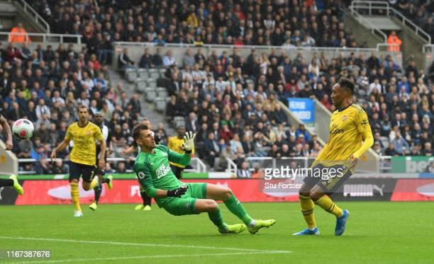 Arsenal player PierreEmerick Aubameyang scores the winning goal past Newcastle goalkeeper Martin Dubravka during the Premier League match between...