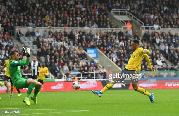 Arsenal player PierreEmerick Aubameyang scores the winning goal past Newcastle goalkeeper Martin Dubravka during the Premier League match between...