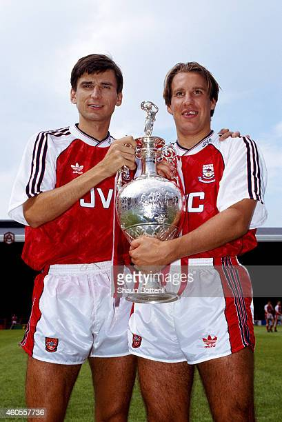 Arsenal players Alan Smith and Paul Merson pictured with the previous seasons League Division One trophy at a pre season photocall at Highbury on...
