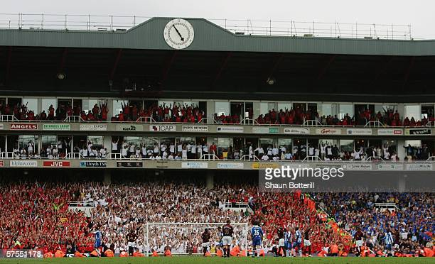 Arsenal players and fans celebrate in front of the Clock End stand as the final whistle goes at the end of the Barclays Premiership match between...