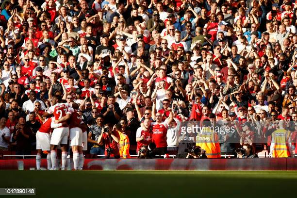 Arsenal players and fans celebrates the opening goal an own goal scored by Craig Cathcart of Watford during the Premier League match between Arsenal...