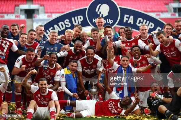 Arsenal players and staff celebrate with the FA Cup Trophy following their team's victory inthe FA Cup Final match between Arsenal and Chelsea at...
