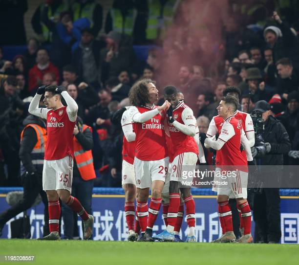 Arsenal players and supporters celebrate the first equalising goal scored by Gabriel Martinelli during the Premier League match between Chelsea FC...