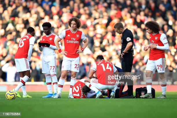 Arsenal players around Callum Chambers as he lays injured during the Premier League match between Arsenal FC and Chelsea FC at Emirates Stadium on...