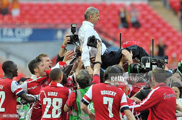 Arsenal players carry their French manager Arsene Wenger as they celebrate after winning the English FA Cup final match against Hull City at Wembly...