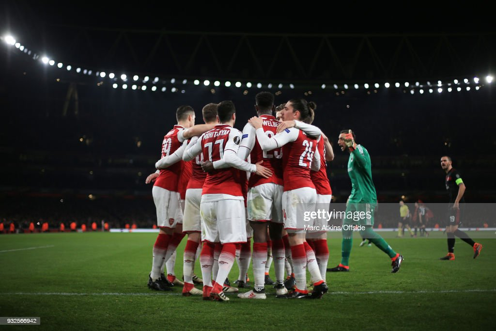 Arsenal players celebrate their 1st goal as Gianluigi Donnarumma and Leonardo Bonucci of AC Milan continue their protest during the UEFA Europa League Round of 16 2nd leg match between Arsenal and AC MIian at Emirates Stadium on March 15, 2018 in London, England.