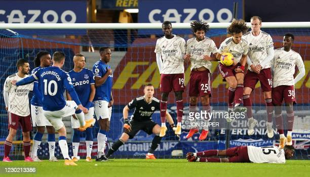 Arsenal players form a wall to defend a free kick taken by Everton's Icelandic midfielder Gylfi Sigurdsson during the English Premier League football...