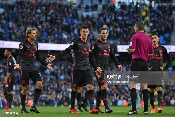 Arsenal players gestures to referee Michael Oliver after Arsenal's Spanish defender Nacho Monreal fouls Manchester City's English midfielder Raheem...