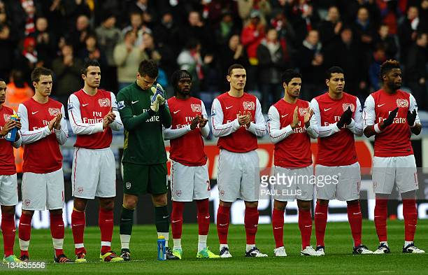 Arsenal players join the minute's applause for Wales manager Gary Speed who died last weekend before the English Premier League football match...