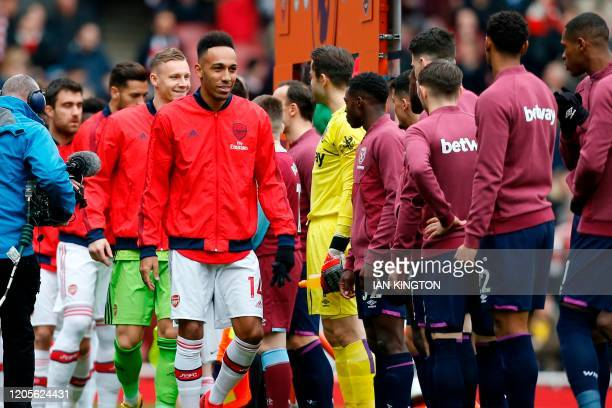 Arsenal players led by Arsenal's Gabonese striker PierreEmerick Aubameyang walk past West Ham players instead of the usual handshakes before the...