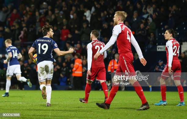 Arsenal players look dejected as Jay Rodriguez of West Bromwich Albion celebrates as he scores their first and equalising goal from the penalty spot...