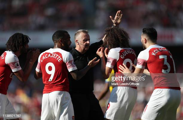 Arsenal players surround referee Jon Moss during the Premier League match between Arsenal FC and Crystal Palace at Emirates Stadium on April 21 2019...