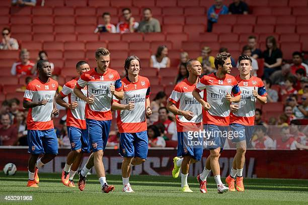 Arsenal players warm up during the first team training session at the Emirates stadium in north London, England on August 7, 2014. AFP PHOTO/Leon...