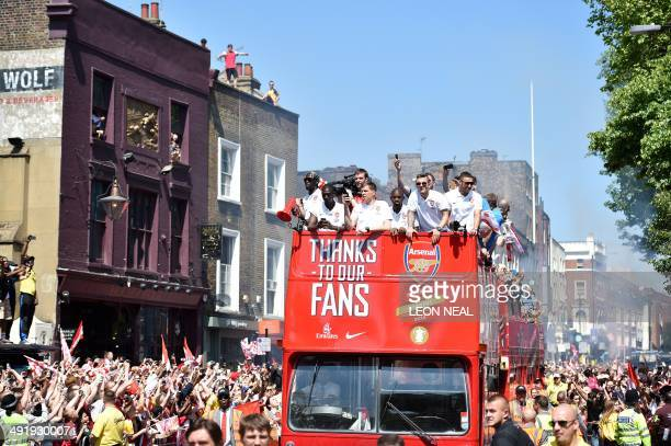 Arsenal players wave to fans from the top of an open topped bus during the Arsenal victory parade in London on May 18 following their win in the...