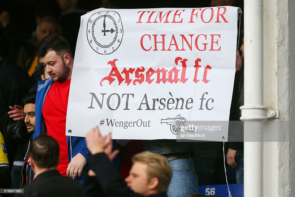 Arsenal supporter holds a banner asking to replace manager Arsene Wenger after the Barclays Premier League match between Everton and Arsenal at Goodison Park on March 19, 2016 in Liverpool, England.
