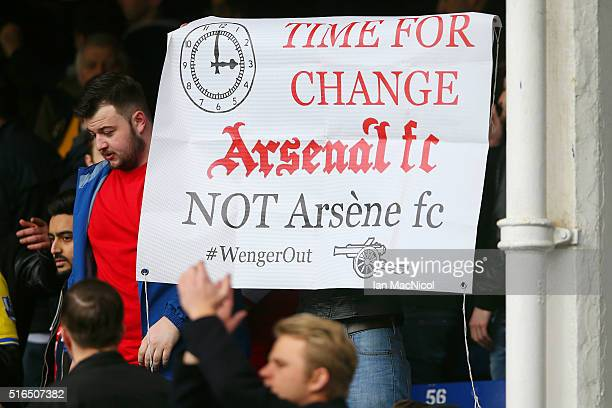 Arsenal supporter holds a banner asking to replace manager Arsene Wenger after the Barclays Premier League match between Everton and Arsenal at...