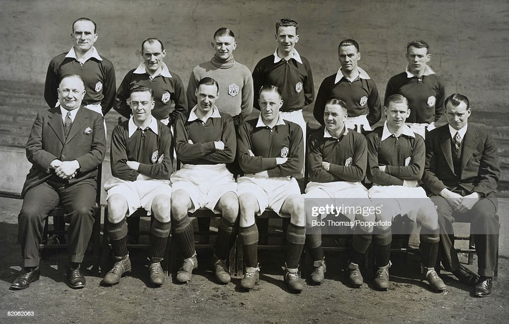 Arsenal team group prior to the 1932 FA Cup Final. Back row (left-right): Tom Parker, Charlie Jones, Frank Moss, Herbie Roberts, Bob John, Tom Black. Front row: Herbert Chapman (Manager), Joe Hulme, David Jack, Jack Lambert, Alex James, Cliff Bastin, Tom Whittaker (trainer). (Photo by Bob Thomas/Popperfoto/Getty Images).