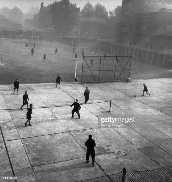 Arsenal team members training behind the clock end at Highbury Stadium in North London. Original publication : Picture Post - 5596 - 'A' Is For...